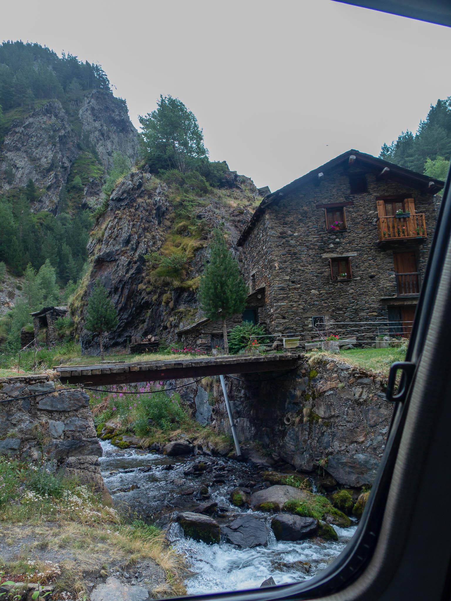 Haus am Fluss in Tor, Spanien, Holzbrücke über den Fluss