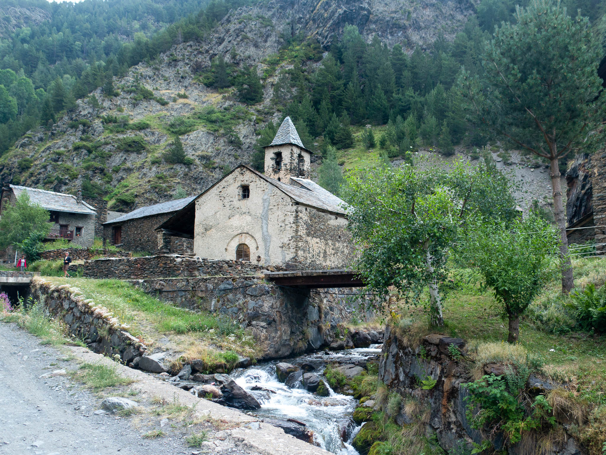 verfalle Kirche in Tor, Spanien, im Vordergrund ein Fluss