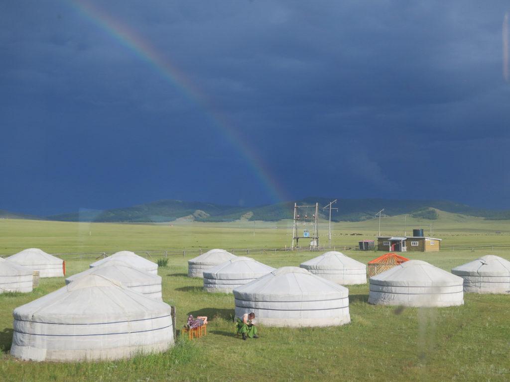 Jurten in der Mongolei, hinten dunkelgrauer Himmel mit einem Regenbogen