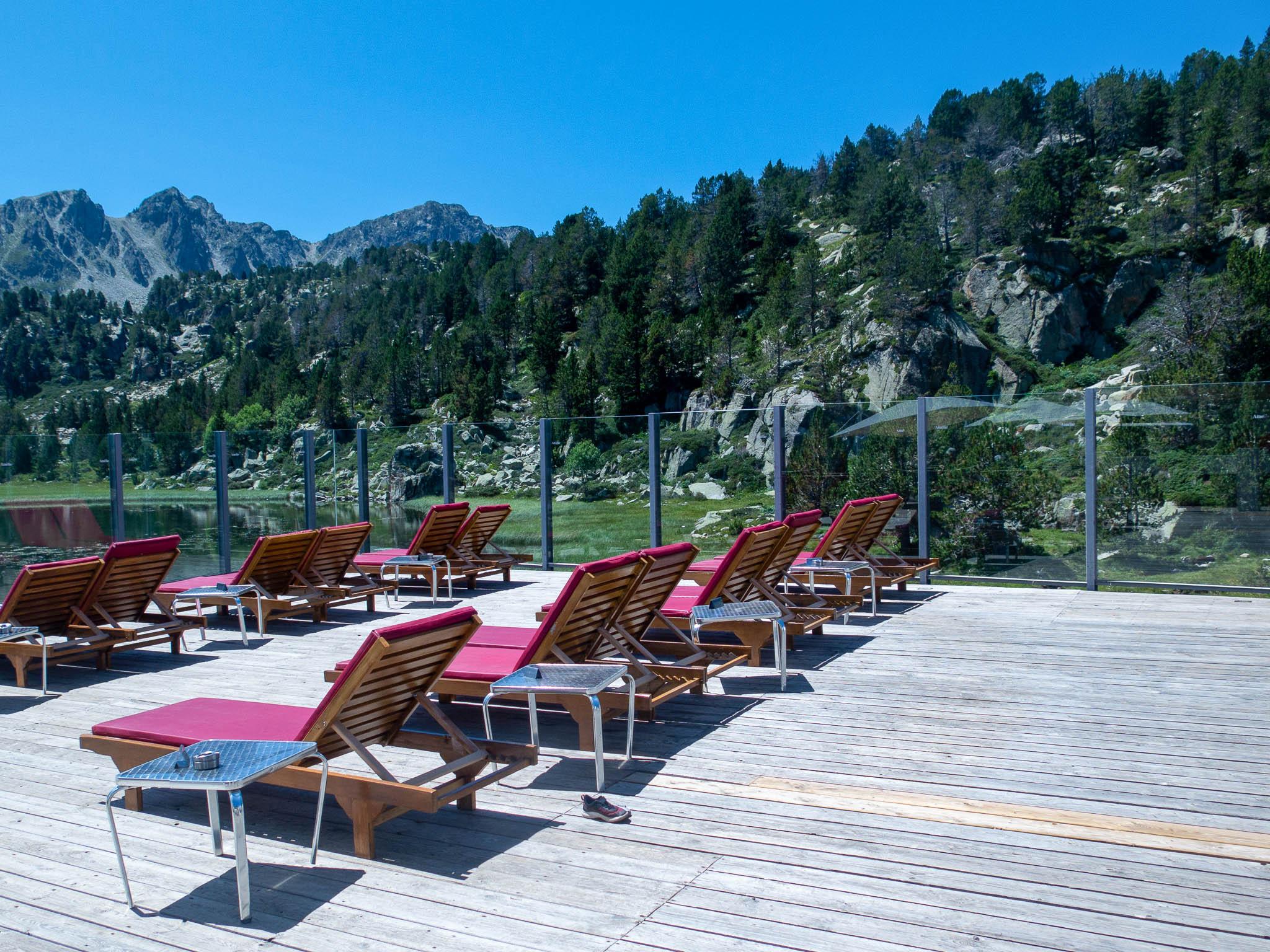 Terrasse Llac dels Pessons Andorra Grandvalira, Sonnenliege, im Hintergrund eine See und Berge